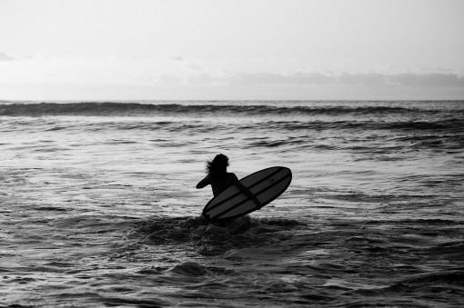 Surferin trägt ihr Surfboard durch die Brandung