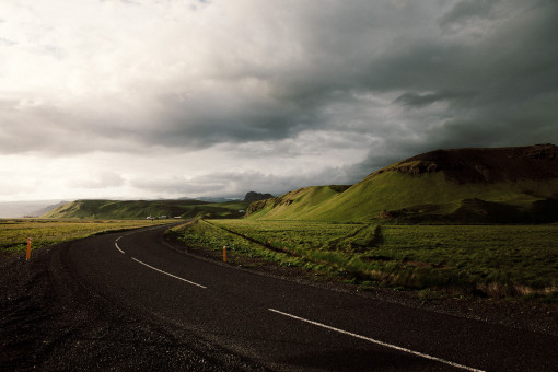 Eine zweispurige Strasse mit einer Rechtskurve in grüner Landschaft