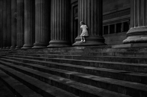 An einer Säule spielendes Mädchen, Treppen im Vordergrund