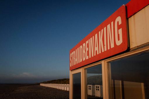 Reihe von Umkleidekabinen am Strand, Schild mit dem Wort Strandbewaking im Vordergrund