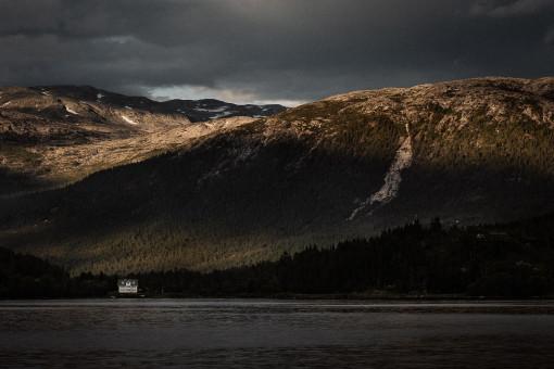 Einsames Haus im Fjord vor bewaldetem Berghang