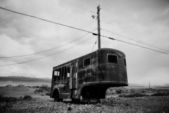 Verfallener Anhänger in öder Landschaft, Strommast mit Leitungen.