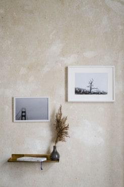 Wand mit zwei Bildern in weissen Rahmen, Messingregal mit Vase und Trockenpflanze